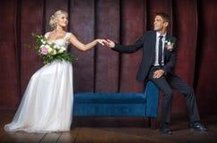 Le marié tient la main de la jeune mariée Photographie stock libre de droits