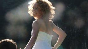 le marié tient la main de la jeune mariée contre des corrections de lumière du soleil banque de vidéos