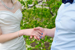 Le marié tient la main de sa jeune mariée en plan rapproché de nature Photographie stock