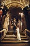 Le marié tient la main du ` s de jeune mariée étant assortie à elle en haut dans une vieille construction Photos stock