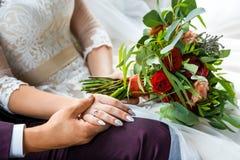 Le marié tient la main du ` s de jeune mariée en plan rapproché Image libre de droits