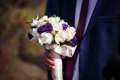Le marié tient le bouquet des fleurs blanches et pourpres Photo stock