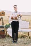 Le marié tient le chien dans des ses bras et sourit à l'appareil-photo au fond de composition de vintage dans Photos libres de droits