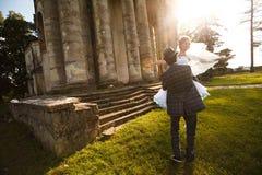 Le marié tient sa belle jeune mariée sur l'herbe de fond et Photographie stock libre de droits