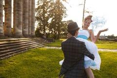 Le marié tient sa jeune mariée de sourire sur l'herbe de fond, colu Photo libre de droits