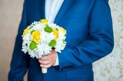 Le marié tient un bouquet lumineux image libre de droits