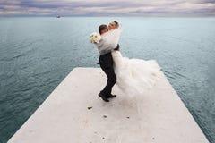 Le marié tourbillonne sa jeune mariée par la voie de maritime Images libres de droits