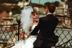 Le marié tourbillonne une jeune mariée sur le toit avec un grand paysage urbain de Lviv Photos libres de droits