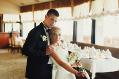 Le marié viril tient les épaules de la jeune mariée tendrement Photos stock