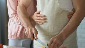 Le mari coupe en tranches maladroitement le poivre, épouse vient pour aider, étreindre, reconnaissant pour le dîner clips vidéos