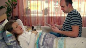 Le mari d'homme avec la tablette amusent sa femme malade d'épouse dans le lit clips vidéos