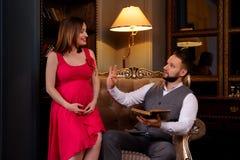 Le mari d'une épouse enceinte est livre de lecture images stock