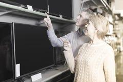 Le mari d'une cinquantaine d'années et l'épouse choisissent pour eux-mêmes la TV au centre Image libre de droits