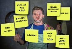 Le mari de maison occupé drôle avec le composé de casserole et de fer de cuisine avec les notes de post-it jaunes est parti par s Photo libre de droits