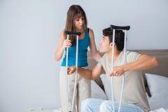 Le mari de soutien de jeune épouse sur la béquille après blessure Photographie stock libre de droits