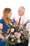 Le mari donne des fleurs à son épouse Images stock