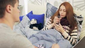 Le mari donne l'eau de boissons à l'épouse malade dans le lit banque de vidéos