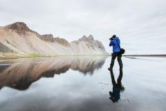 Le mari est une position de photographe sur la surface de l'eau à la côte de l'Islande dans Stokksnes photos stock