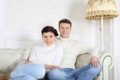 Le mari et l'épouse aux pieds nus de sourire dans des jeans s'asseyent sur le sofa blanc Photo libre de droits
