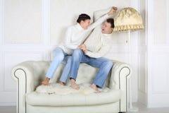 Le mari et l'épouse de sourire s'assied dessus de retour du sofa blanc Images stock