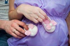 Le mari et l'épouse, la maman et le papa tiennent des mains avec des butins sur le ventre Grossesse photos stock