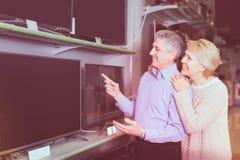 Le mari et l'épouse mûrs choisissent pour eux-mêmes la TV au centre de l'EL Photographie stock