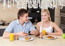 Le mari et l'épouse prennent le petit déjeuner dans la cuisine Photo stock