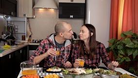 Le mari et l'épouse s'asseyent dans la cuisine à la table causant et prenant le déjeuner Sur la table sont la salade, légumes banque de vidéos