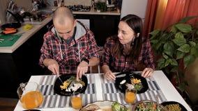 Le mari et l'épouse s'asseyent dans la cuisine à la table et dîner Sur la table, salade, légumes, verts, poulet, maïs banque de vidéos