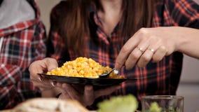 Le mari et l'épouse s'asseyent dans la cuisine à la table, l'épouse met la salade végétale sur le plat du mari clips vidéos