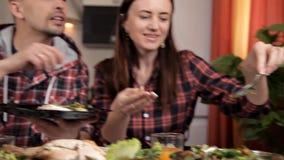 Le mari et l'épouse s'asseyent dans la cuisine à la table, l'épouse met une salade végétale sur le plat du mari banque de vidéos