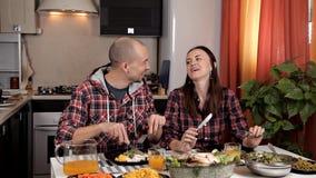 Le mari et l'épouse s'asseyent dans la cuisine à la table et prennent le déjeuner Sur la table sont la salade, légumes, verts clips vidéos