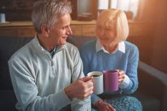 Le mari et l'épouse s'asseyent ensemble et thé potable des tasses Images stock
