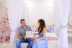 Le mari et l'épouse se donnent des cadeaux de Noël dans le spaci lumineux Photo stock