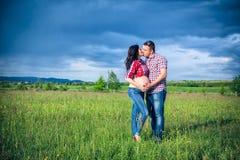 Le mari et son épouse enceinte marchent au sunse Photographie stock libre de droits