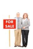 Le mari mûr et l'épouse se tenant prêt en vente signent Photographie stock libre de droits