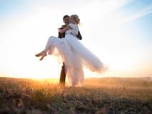 Le mari porte son épouse aimée dans des ses bras, dans le coucher de soleil Photo libre de droits