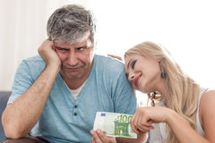 Le mari triste donnent 100 euros à l'épouse de golddigger Image stock
