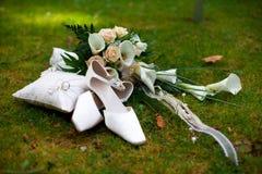 Le mariage chausse les boucles et le bouquet Photographie stock