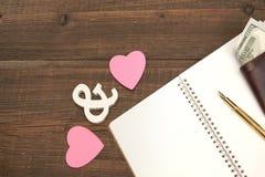 Le mariage coûte le concept Coeurs, stylo, papier, argent sur Backgro en bois Photo stock