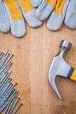 Le marteau de griffe d'image de Copyspace cloue les gants protecteurs sur la BO en bois Images stock