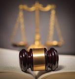 Le marteau du juge au milieu d'un livre de loi Images stock
