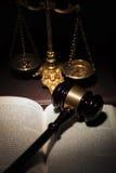 Le marteau du juge sur un livre près d'échelle d'or Photographie stock