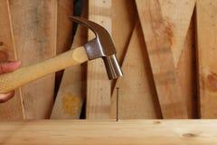 Le marteau a frappé le clou sur le bois photographie stock libre de droits