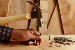 Le marteau a frappé le clou sur le bois photographie stock