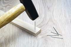 Le marteau martèle un clou dans un bloc en bois photos libres de droits
