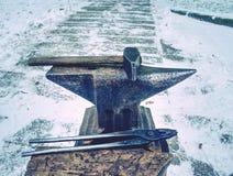 Le marteau se trouve sur l'enclume, lieu de travail de forgeron photographie stock libre de droits
