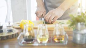 Le ` masculin s de cuiseur remet des concombres de coupe sur un conseil à cuire en bois image libre de droits