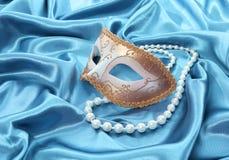 Le masque d'or de scintillement et le collier de perle sur la soie de turquoise drapent Photographie stock