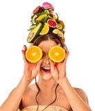 Le masque de cheveux des fruits sur la prise de tête de femme divise en deux les yeux fermés oranges Photographie stock libre de droits